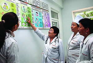 Photo of a health care supervisor instructing three health care workers and pointing to a poster on breastfeeding.