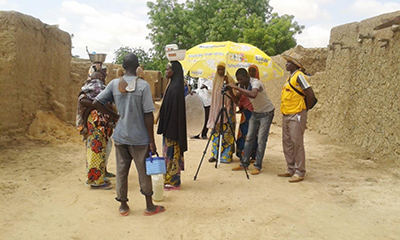 Photo of a video production crew filming two women with children carrying baskets on their head.