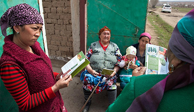 Photo: four women and and one infant. The women are looking at a SPRING publication on food storage.