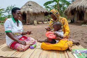 Photo of a woman in a USAID/SPRING shirt sitting on a mat on the ground with a mother holding her child in her arms. The mother is feeding the child with a spoon.
