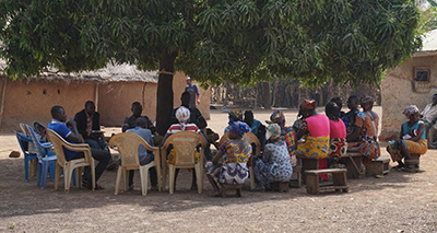 Photo of a counseling group meting in a circle under a large tree.