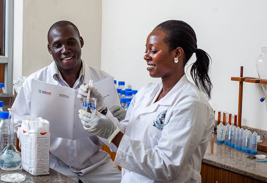 "Photo of a man and a woman at work in a lab. Caption: ""Thomas Okoth and Justine Nabuuma of the Uganda Industrial Research Institute (UIRI) perform an iron spot test to determine if maize flour marked with the fortification logo is actually fortified."""