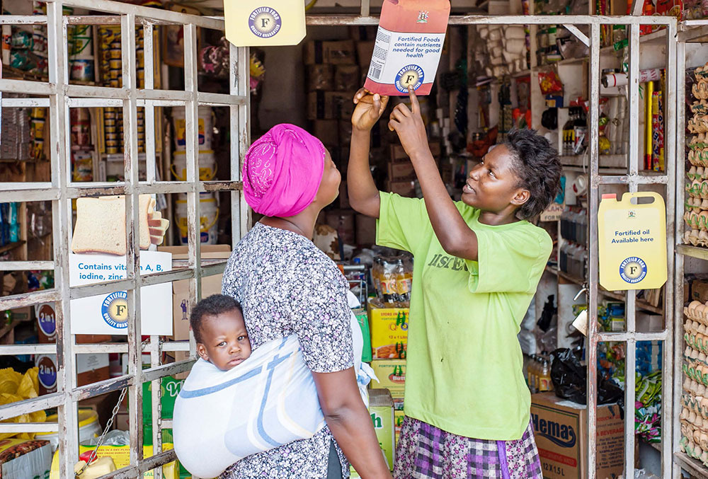 Shopkeeper Winnie Nanyonga explains food fortification to her client, Jessica Namusoke.