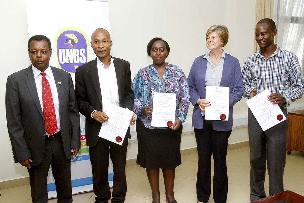 During a laboratory recognition ceremony, representatives of accredited laboratories pose with their certificates of recognition with Ben Manyindo (far left), the executive director of UNBS.