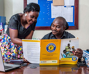 Abdul Nuldin Katongole and Jolly Ruyonga, traders who work with maize millers, read a factsheet on food fortification.
