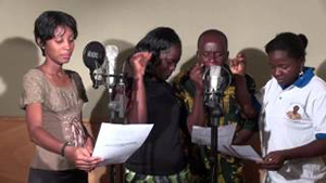 People speak into microphones, reading from a script. Courtesy of Development Media International.