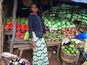 Woman stands in front of produce stand