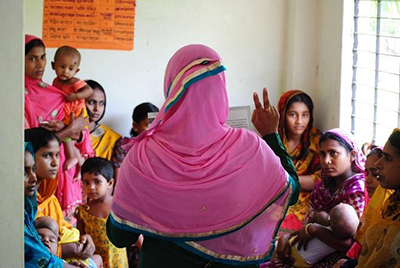 Photo of a woman speaking to a group of women and children.