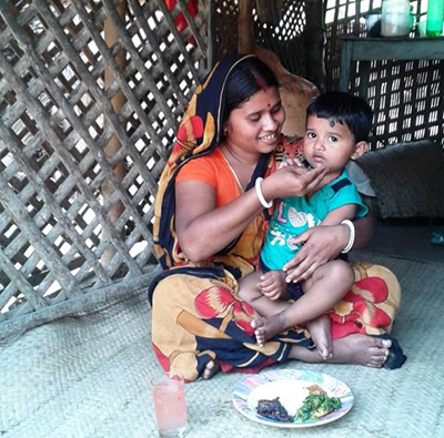 Photo of a woman feeding her child from a plate set before them.