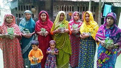 Image of FNS participants displaying vegetable seedlings they received to plant in their gardens.