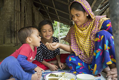 A Bangladeshi woman sits on a blanket with her two young children. There is a plate of food on the blanket and she is holding out her hand with food in it to feed the younger child.