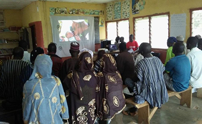"Photo of about twenty people gathered to watch a video at an advocacy video dissemination session for opinion leaders in Gbullung Area Council. Caption: ""Opinion leaders in Gbullung Area Council, Kumbungu District attend an advocacy video dissemination session."""