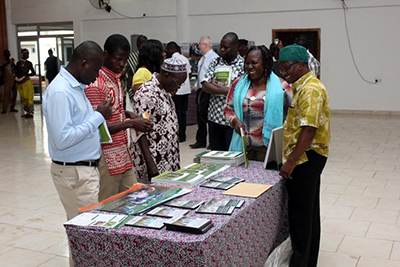 "Photo of a woman receiving a group of four visitors at an event table.  Caption: ""SPRING's agriculture advisor receives visitors admiring SPRING's training manuals on display at the learning and sharing event in Tamale."""