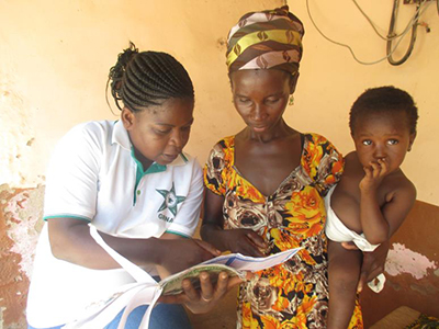 "Photo of a mother and her child getting assistance from a health volunteer. Caption: ""A community health volunteer tracks a child's growth chart in Garu District."""