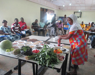"Photo of a woman, standing at a table with different kinds of food, making a presentation to people gathered in a room. Caption: ""A health worker demonstrating how to select from different food groups to achieve a diet recommended for anemia prevention."""