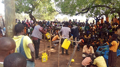 "Photo of students demonstrating the construction of a tippy tap in front of a large group. Caption: ""School pupils participate in a tippy tap construction demonstration session in their community."""