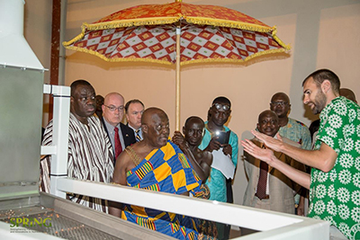 "Photo of ten or so people gathered for the commissioning of a groundnut roasting facility. Caption: ""Project Peanut Butter Technical Manager Martin Histand (far right) explains how components of the groundnut-roasting equipment are operated to dignitaries, including the Royal Adontenhene (representative of the Otumfuo, Ashanti King, in traditional attire). Looking on are the US Ambassador to Ghana, Mr. Robert P. Jackson (second from left) and Ghana's Minister for Business Development, Hon. Mohammed Ibrahim"
