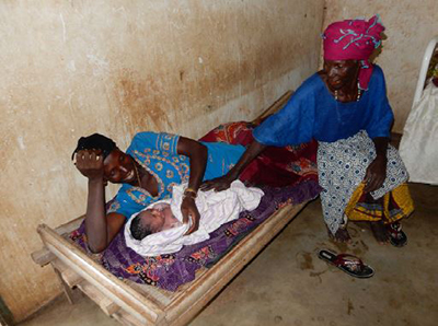 "A mother lying on a cot with her child as an older woman/relative sits with them. Caption: ""This mother of seven children, who is a small-scale Guinean farmer, is a primary target audience for nutrition-specific and nutrition-sensitive agriculture interventions."""