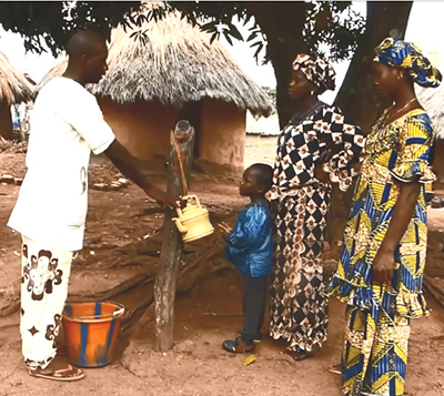 Photo of a man, two women, and a child standing at at tippy-tap. Caption: This father creates a household handwashing station (tippy tap) with locally available materials.