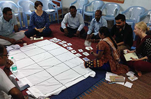 Photo of a group of people during a training. Caption: Enumerators practice facilitating a daily activity chart exercise during training.