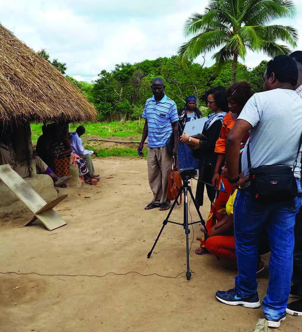 Photo of a group of women and men, standing outside a home, working on a video.
