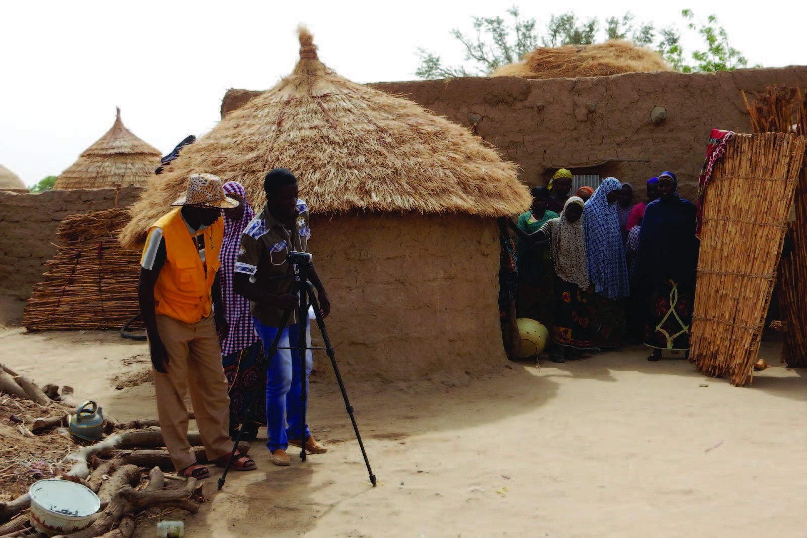 "Photo of two men and a woman behind a camcorder, preparing to make a video of a family. Caption: ""Community videos on optimal MIYCN and hygiene practices are produced by local video production hubs and disseminated in existing community groups by community volunteers."