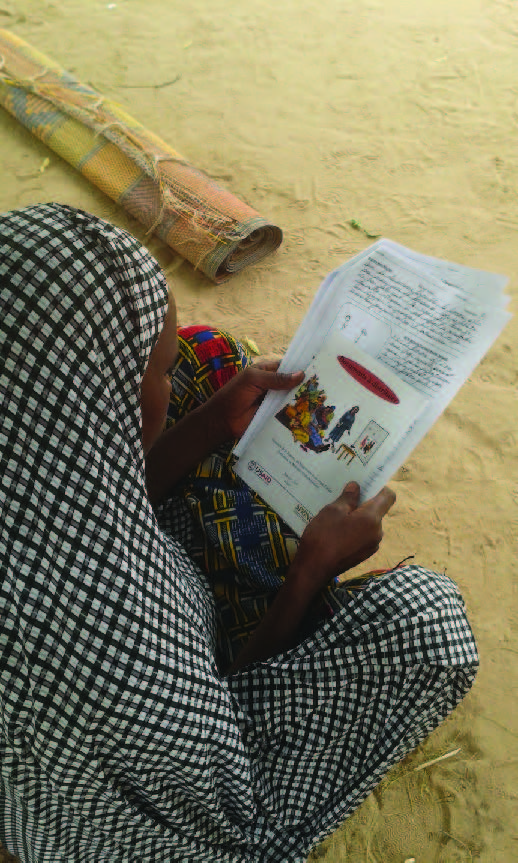 Photo of a woman, sitting on the ground, reading information supplied by the project.
