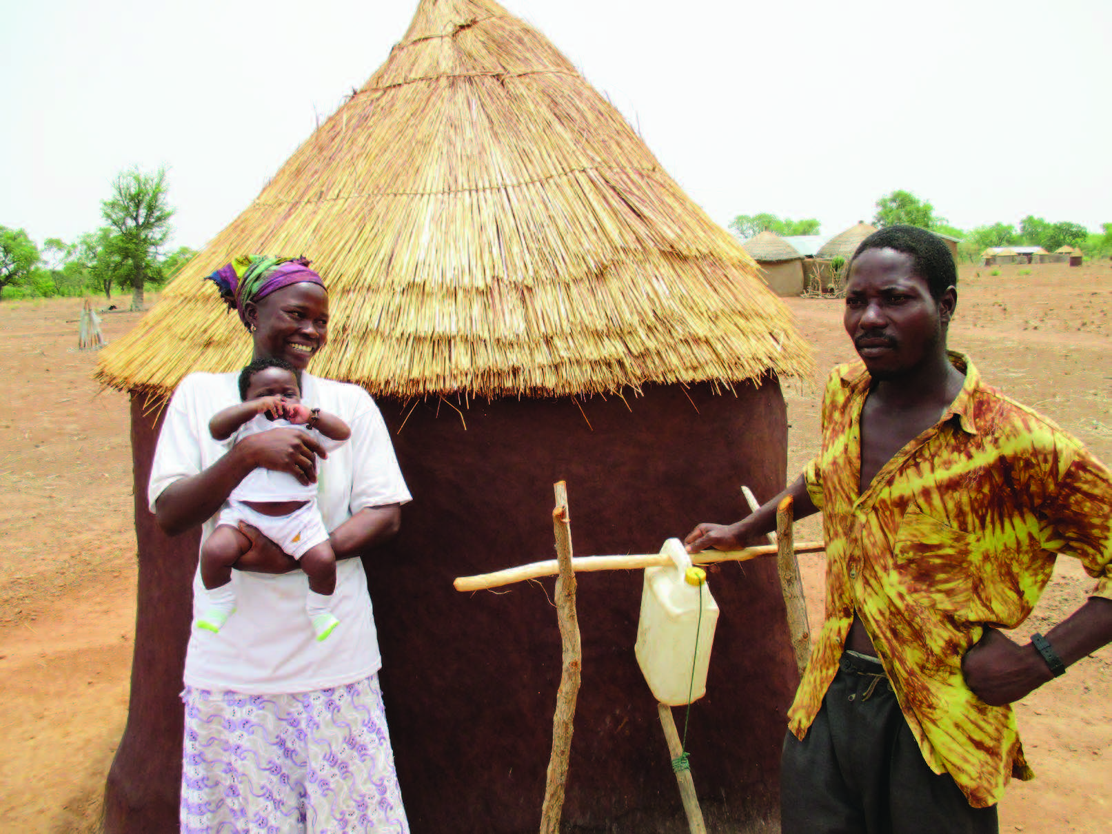 "Photo of a family (man, woman, infant) standing outside an outhouse that has a tippy tap next to it. Caption: ""Participants of our SPRING/Ghana program create a drama to promote nutrition-sensitive water, sanitation, and hygiene (WASH) practices using a Tippy Tap. For more, please visit: www.spring-nutrition.org/about-us/activities/wash-1000-and-community-led-total-sanitation-ghana."""