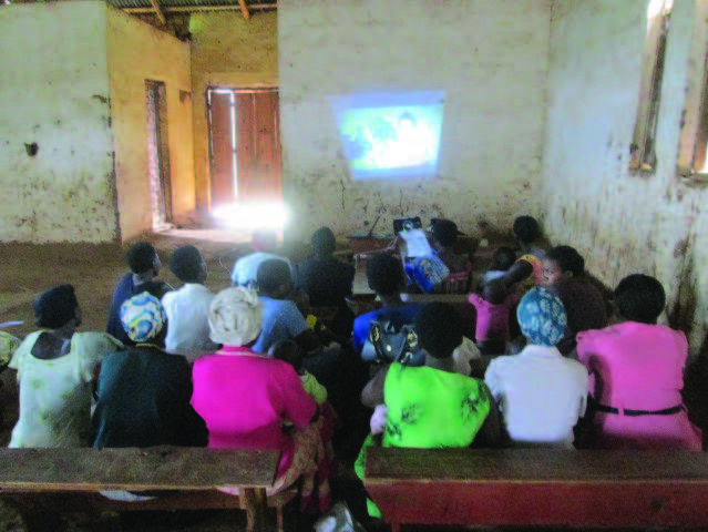 "Photo of about twenty women sitting on benches in a large room, watching a video. Caption: ""Women gather to watch a video testimonial that uses emotion-based drivers related to child health as part of our SPRING/Uganda ""Great Mothers, Healthy Children"" campaign. For more, please visit: www.spring-nutrition.org/about-us/activities/great-mothers-healthy-children-campaign."""