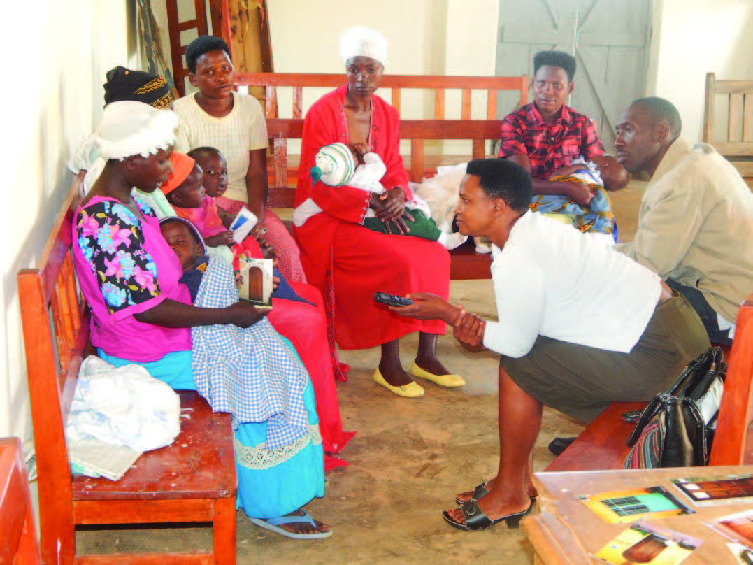 Photo of five women, sitting on benches with their infants, receiving counselling from a woman and a man.