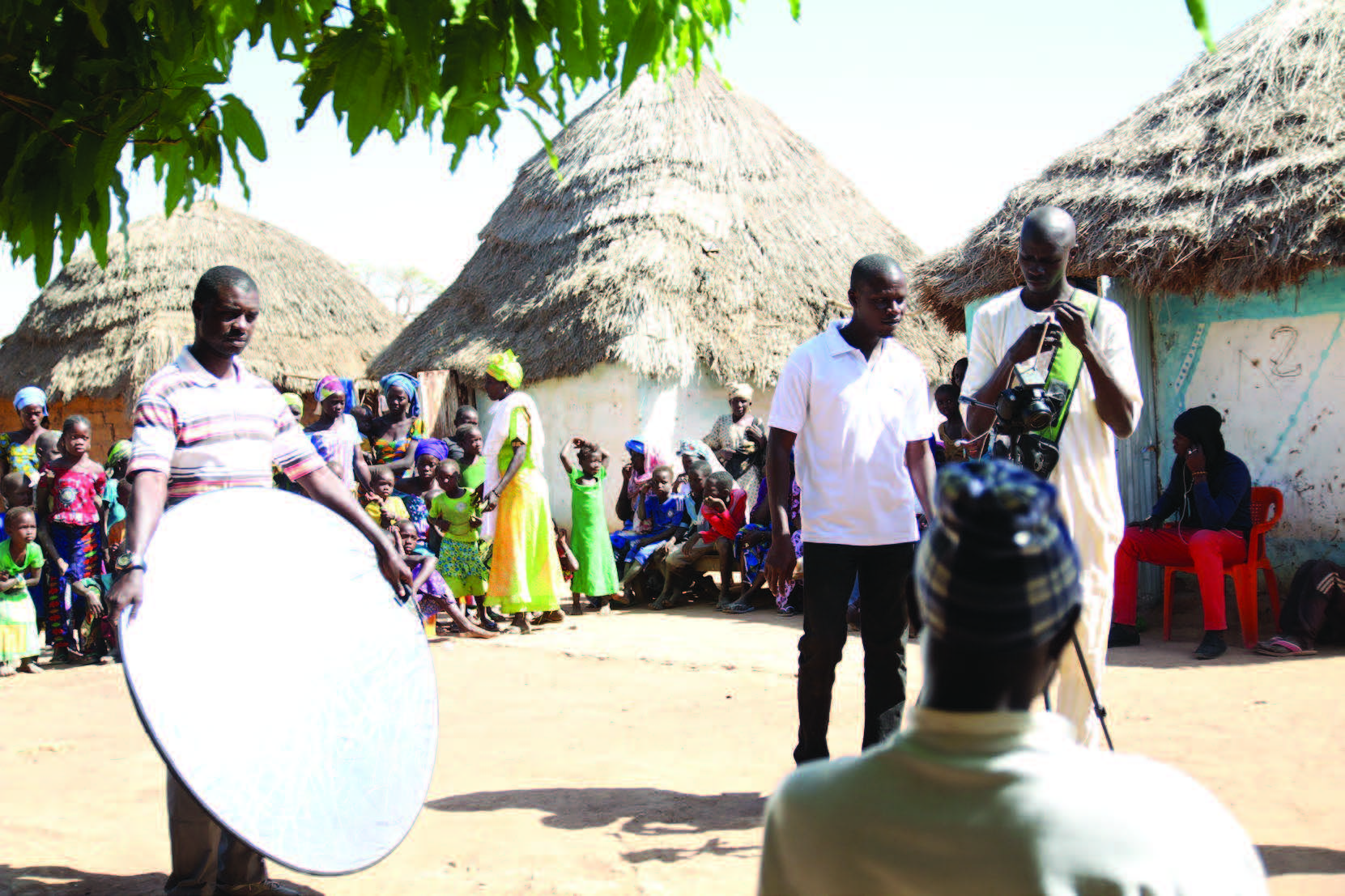 "Photo of three men with a camcorder working on a video, with one man being filmed in front of them, and other women, men, and children in the background by their homes. Caption: ""SPRING/Senegal is working with partners to by operating through existing health, agriculture, and food security programs and using community video and radio. For more on our work in Senegal, please visit: www.spring-nutrition.org/countries/senegal """