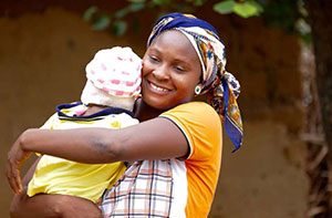 A woman smiles at the camera while holding her baby.