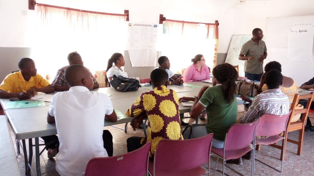 "Photo of about a dozen women and men at a table during a training. Caption: ""Figure 2. Training of Interviewers in Makeni"""