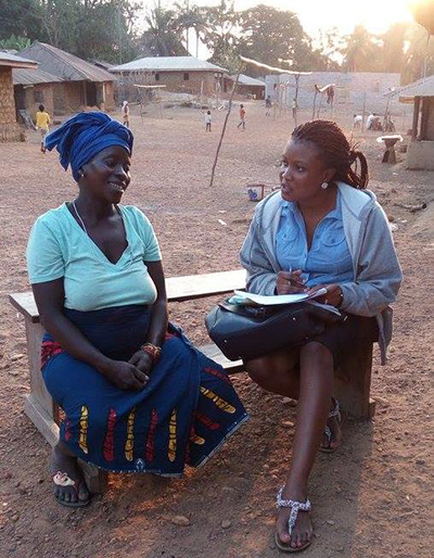 "Photo of a woman staff person from SPRING speaking to a pregnant woman. Caption: ""SPRING staff interview a mother in the Tonkolili region as part of SPRING's barrier analysis."""