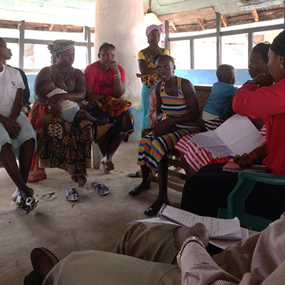 "Photo of a group of about ten women having a discussion in a room. Caption: ""Women farmers in Makali participate in a focus group discussion for AVCA."""