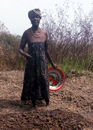 Photo of a woman standing on a bed of dirt, holding a bowl.