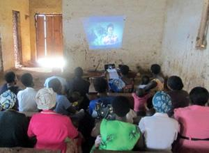 "Photo of about twenty women in a room watching a video projected on a wall. Caption: ""In June 2014, women in a mother's group VHT video session in Ntungamo listen to nutrition messages."""