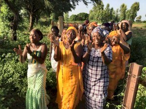 Photo of a group of women walking through a garden singing and clappingn hands.
