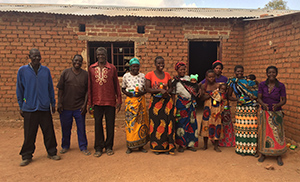 "Photo of three men, six women, one girl, and three infants. They are standing outside a brick building, smiling at the camera. Caption: ""Proud Mawa beneficiares"""
