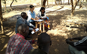 "Photo in which one can see six persons gathered outside for a discussion/presentation. Caption: ""SPRING staff prepare guides for a focus group discussion. Teams of three included a facilitator, a local research assistant, and a notetaker."""