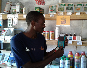 "Photo of a man standing by shelves with different products holding a calculator. Caption: ""A PROFIT+ CAD shows the SPRING team around his store"