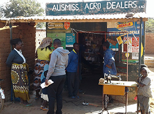 "Photo of a group of people standing outside a store. The sign above the store reads: ""AUSMISS AGRO DEALERS cad"""