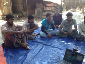 Photo of several men seated outside on a tarp. Phultala focus group discussion (Photo by T. Schaetzel)