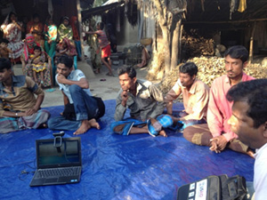 Photo of several men seated outside on a tarp. Rupsa focus group discussion (Photo by T. Schaetzel)