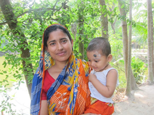 Photo of a mother holding a small infant outside. Wife of one participant (Photo by M. Antal)