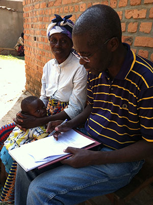 health worker collecting data from woman with young child