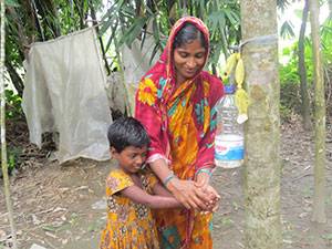 Woman and child washing hands using a Tippy Tap,