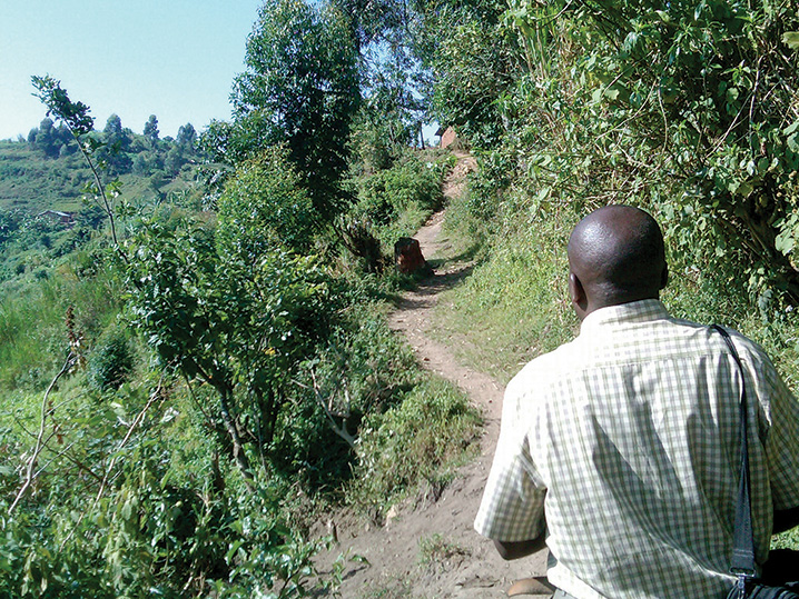 Photo of a data collection supervisor walking up a path on a hillside on the way to a village for data collection (photos credit: Alexis D'Agostino, SPRING).