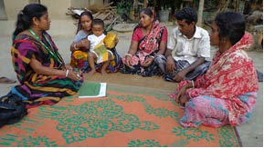 SUnion Facilitator Oloka Biswas speaks to a farmer nutrition school graduate and her family members