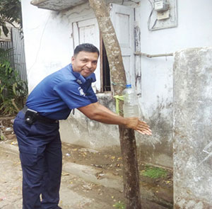 Officer Faridul Islam washes his hands with a tippy tap.